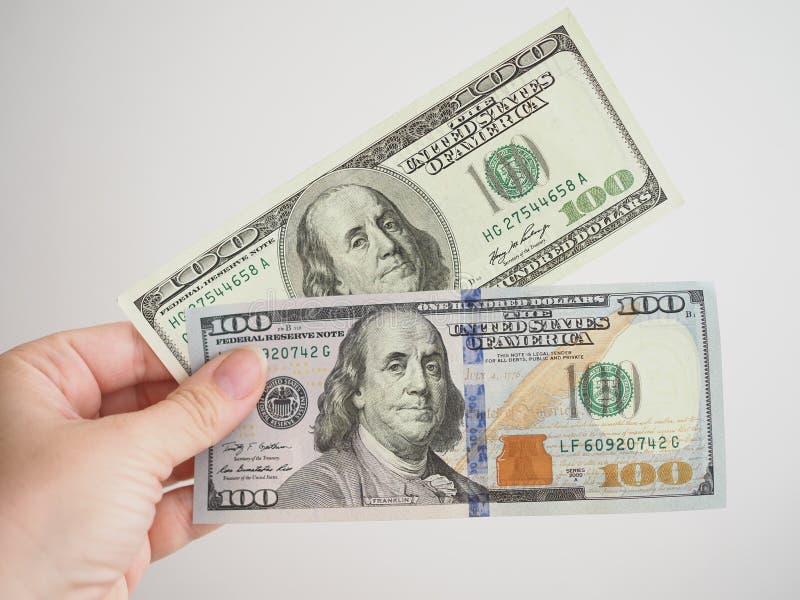 Gammal och ny 100 dollar sedel i en kvinnas hand royaltyfri bild