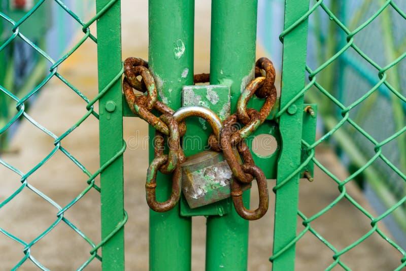 Gammal och rostig hänglås som kedjas fast till en grön dörr i ett staket arkivbilder
