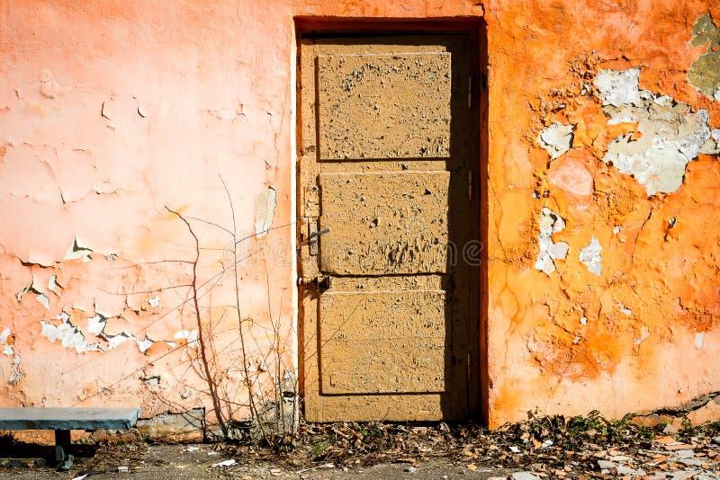 Gammal orange vägg med en dörr royaltyfria bilder