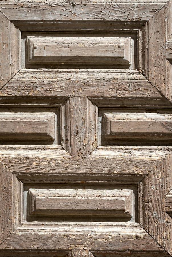 Gammal paneled trädörr; rostigt och ridit ut f?r kupatextur f?r bakgrund brunt tr? royaltyfri foto