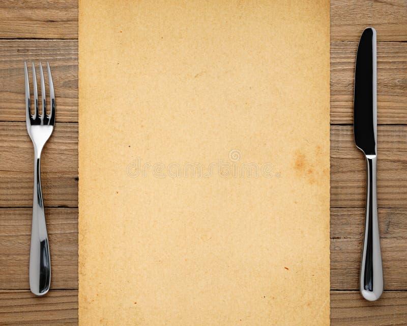Gammal papper, gaffel och kniv arkivfoto
