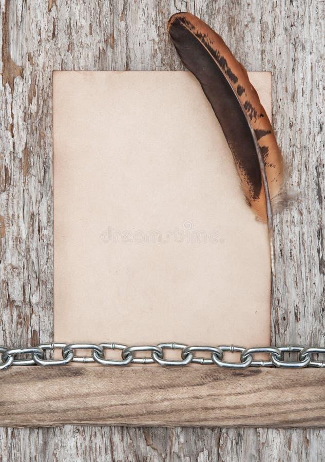 Gammal pappers-, fjäder- och metallkedja på det gamla trät royaltyfria foton