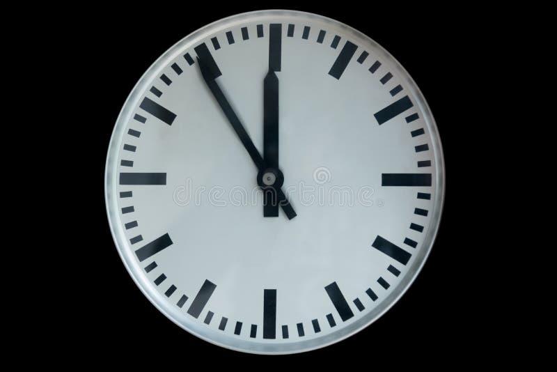 Gammal parallell klocka som visar fem till tolv som isoleras på svart royaltyfria bilder