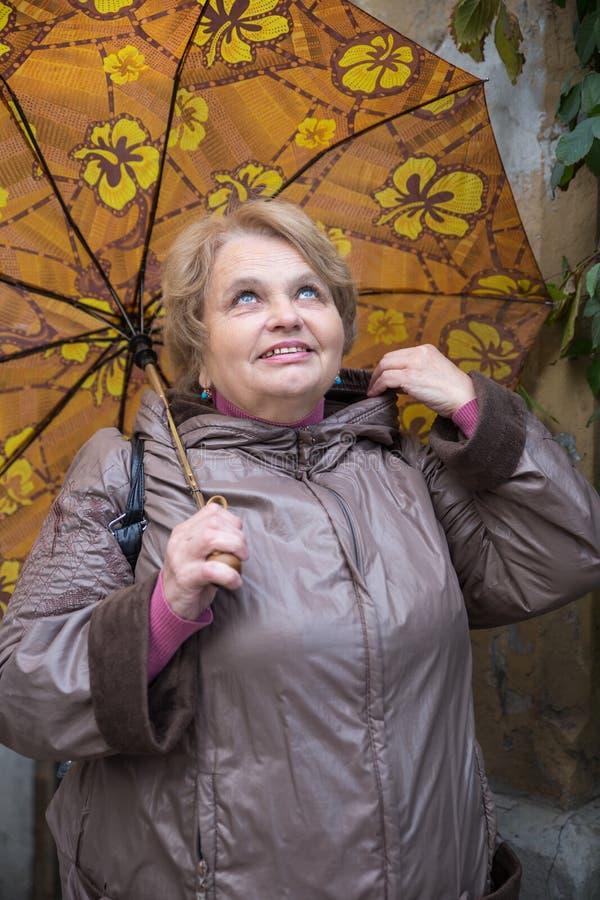 Gammal pensionärkvinna med paraplyet royaltyfria foton