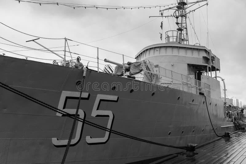Gammal pensionerad stridkryssare som ankras på port royaltyfria foton