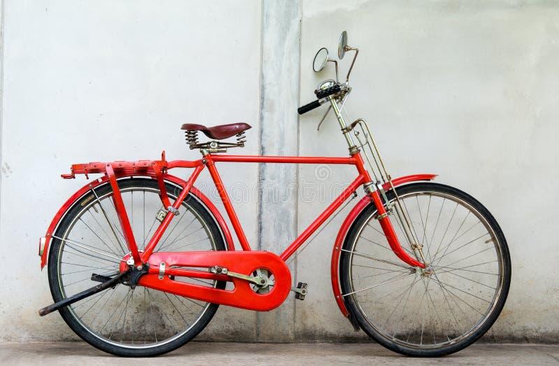 Gammal röd cykel- och cementvägg royaltyfri fotografi
