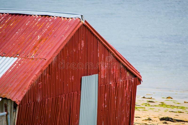 Gammal röd galvaniserad järnladugård på Palm Beach, nord av Sydney, Australien arkivfoton