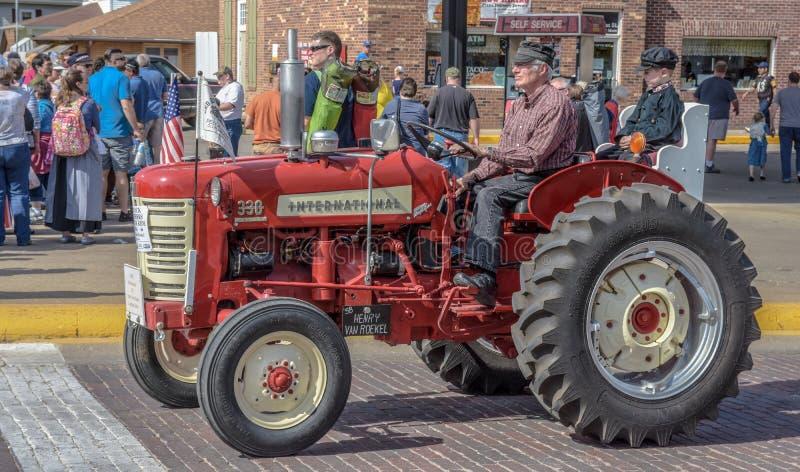 Gammal röd internationell traktor i Pella, Iowa arkivfoto