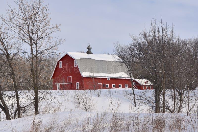 Gammal röd ladugård i vintern arkivbild