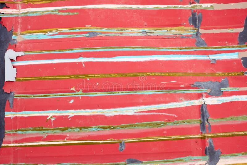 Gammal röd målad yttersida med färgrika band arkivfoton
