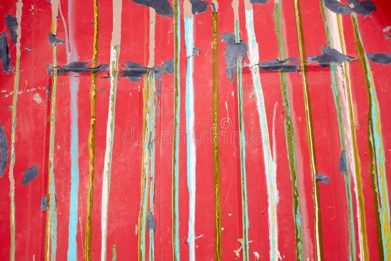 Gammal röd målad yttersida med färgrika band arkivbild