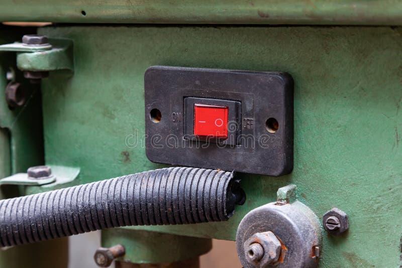 Gammal röd maktströmbrytare på en grön maskin för produktionen och bransch med orden av och på i av positionen Begrepp av royaltyfria foton