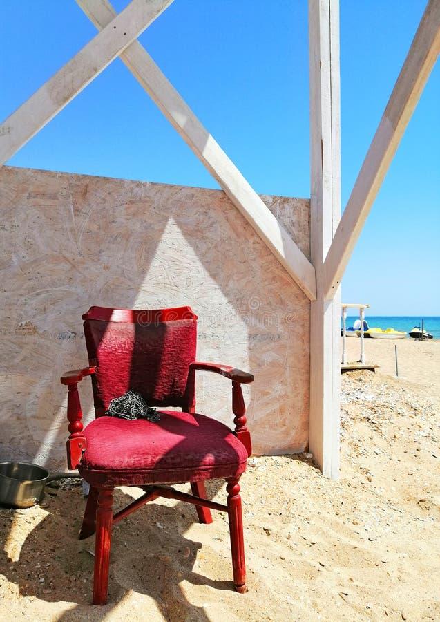 Gammal röd stol på stranden arkivfoton