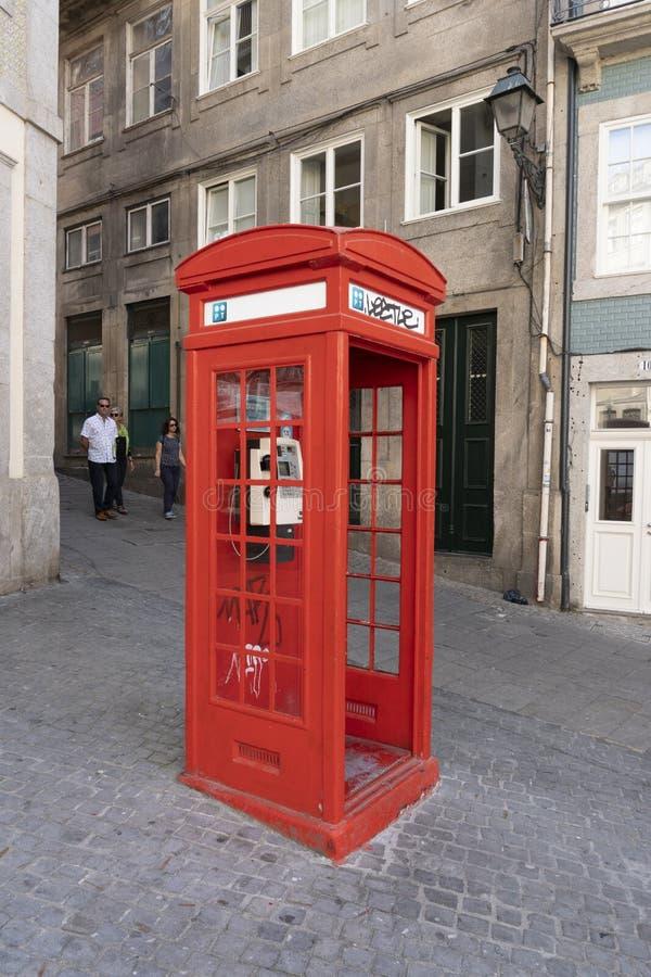 Gammal röd telefonkabin på gatan porto portugal arkivfoto