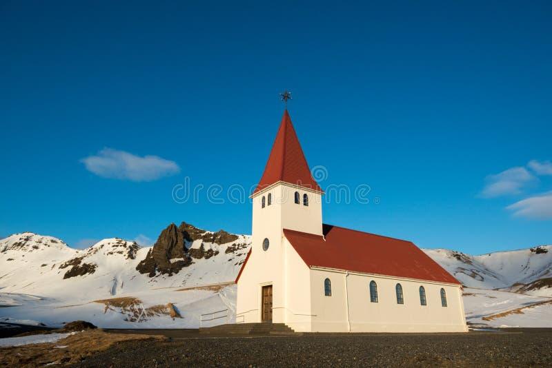 Gammal röd träkyrka på solnedgången, Vik stad, Island royaltyfria bilder