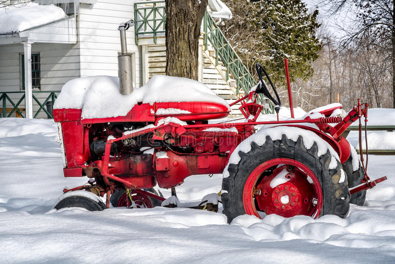 Gammal röd traktor i snö royaltyfria bilder
