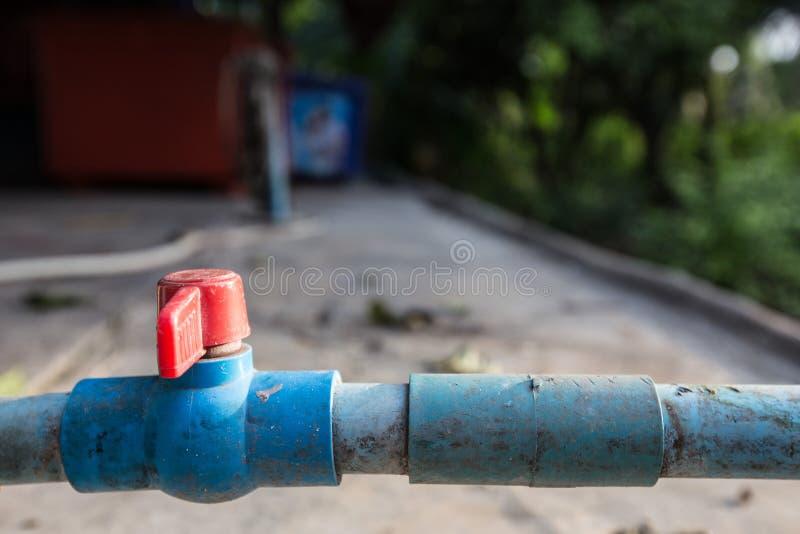 Gammal röd vattenkran på blå rörmokeri arkivfoto