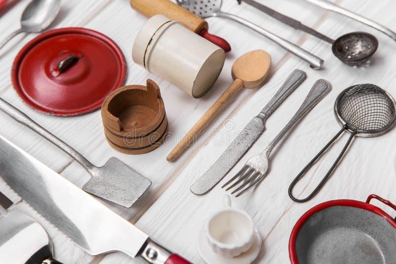 Gammal röda vit dockas kökminiatyrer av tenn och trä Tappning royaltyfria foton