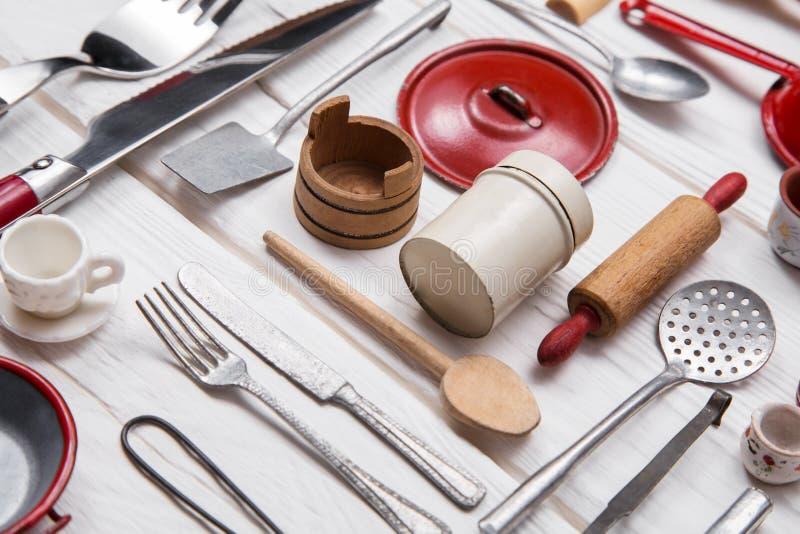 Gammal röda vit dockas kökminiatyrer av tenn och trä Tappning royaltyfri bild