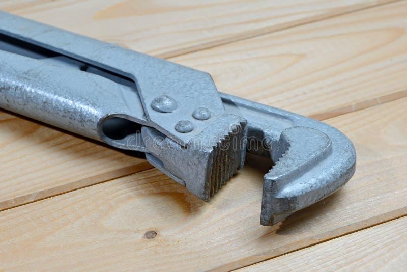 Gammal rörskiftnyckel på en träbakgrund Justerbar skiftnyckel för rörmokare royaltyfri fotografi