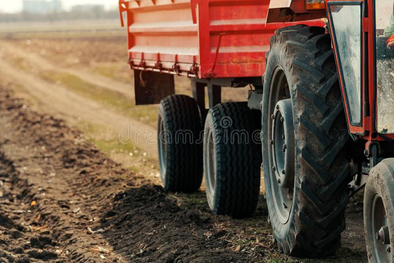 Gammal r?d jordbruks- traktor med sl?pet p? smutsbygdv?gen arkivbild
