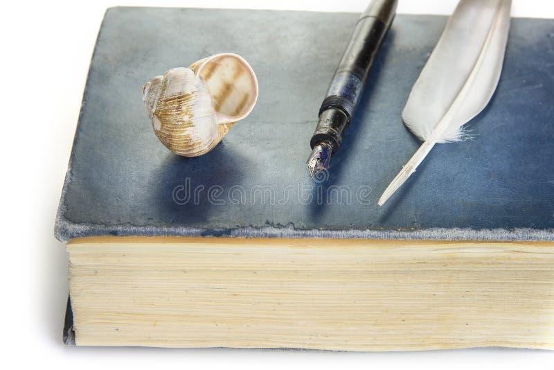 Gammal reservoarpenna med fjädern på en bok royaltyfria foton