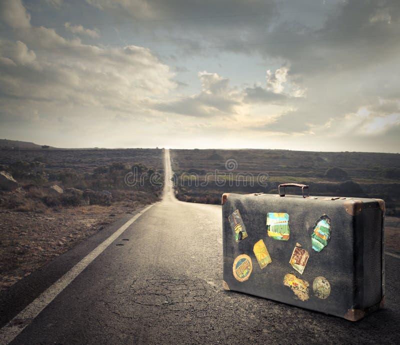 Gammal resväska i mitt av en gata arkivfoto