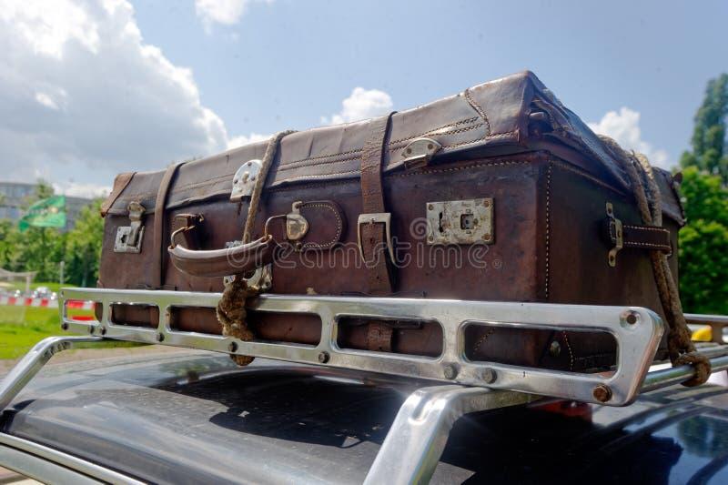 Gammal resväska på biltakkuggen arkivbild