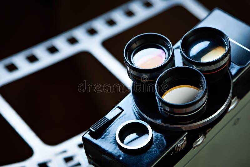 Gammal retro filmkamera på bakgrund av perforeringsfilmen royaltyfri bild