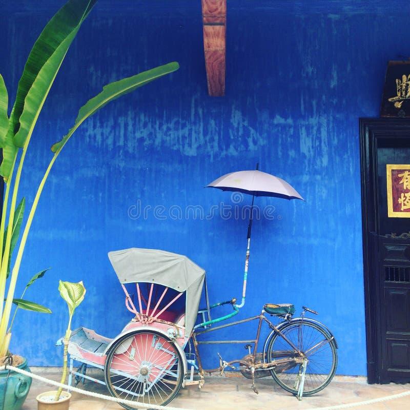 Gammal Rickshaw framme av blåtthuset royaltyfria foton
