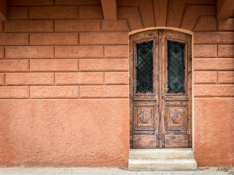 Gammal riden ut brun dörr som göras av trä, orange vägg i Kroatien royaltyfri fotografi