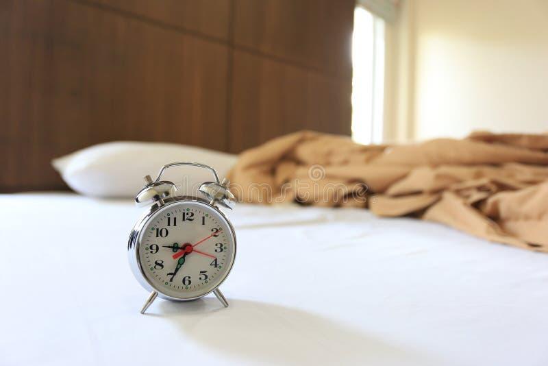 Gammal ringklocka på säng i sovrum fotografering för bildbyråer