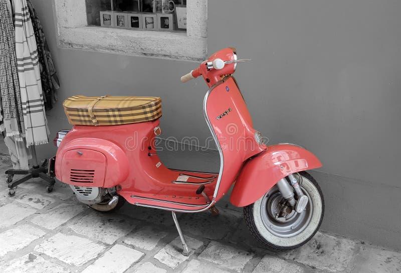 Gammal rosa Vespasparkcykel på gatorna av Kerkyra, Korfu, Grekland royaltyfri bild