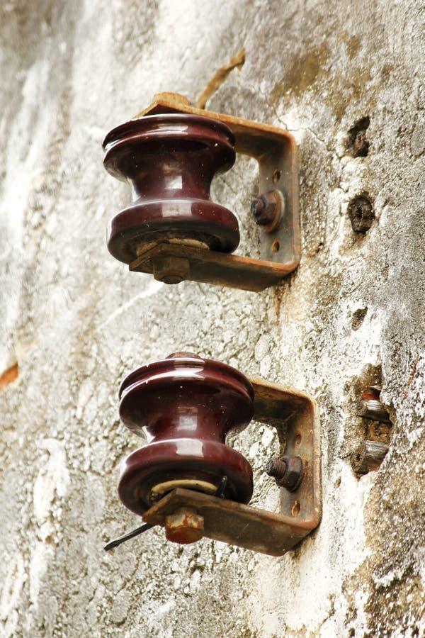 Gammal rost för elektrisk isolator på väggen arkivfoton