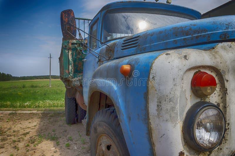 Gammal rosta lastbil eller lastbil utomhus i ett fält royaltyfria bilder