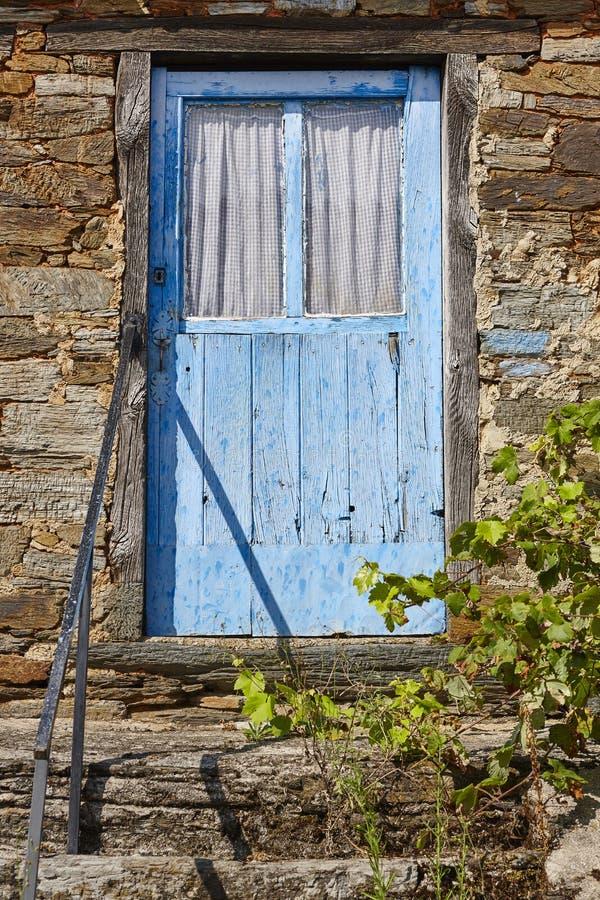 Gammal rostad blå trädörr- och stenhusfasad royaltyfri foto