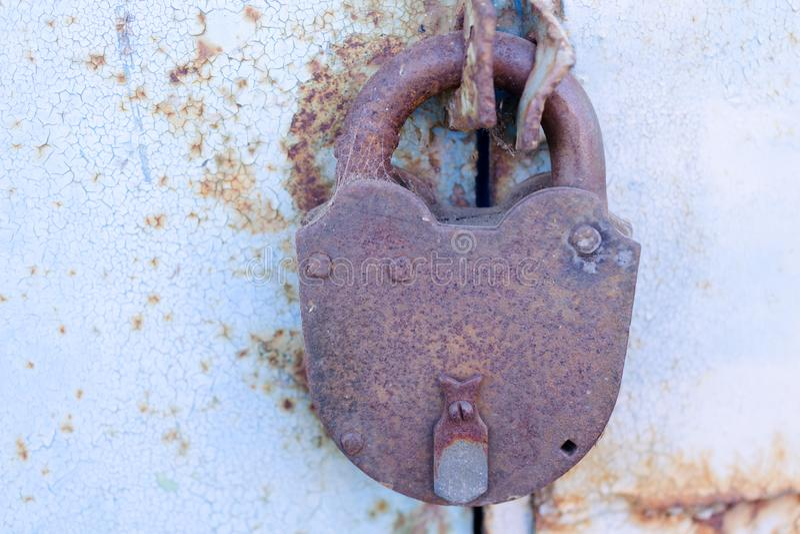 Gammal rostad hänglås på en metalldörr med sprucken blå målarfärg royaltyfri foto