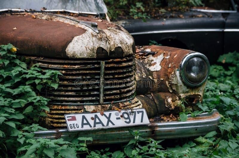 Gammal rostad retro bil Opel Kapitan som överges i trän arkivbilder