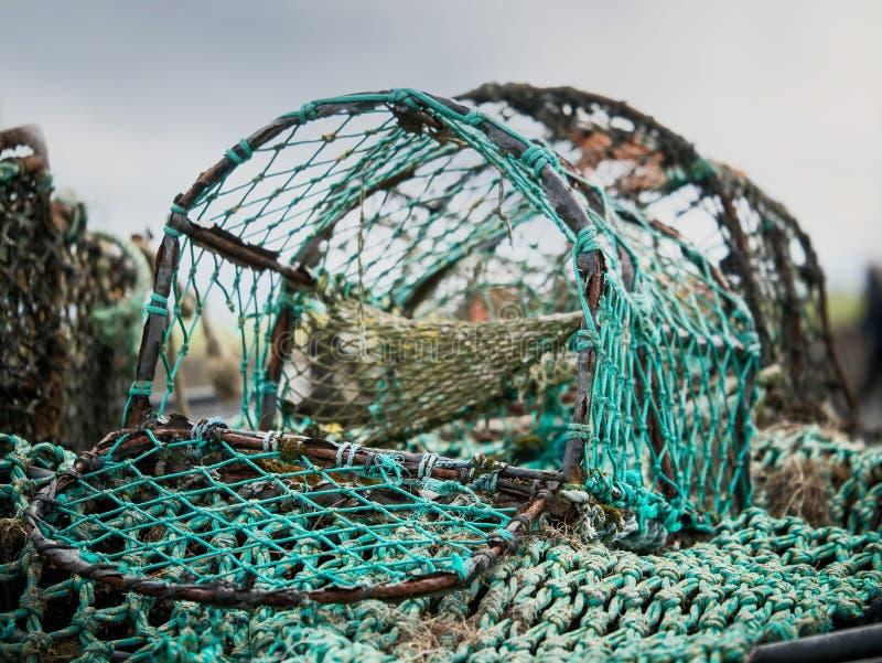 Gammal rostig öppen krabbafälla, selektiv fokus, grönt sönderrivet ingrepp arkivfoto