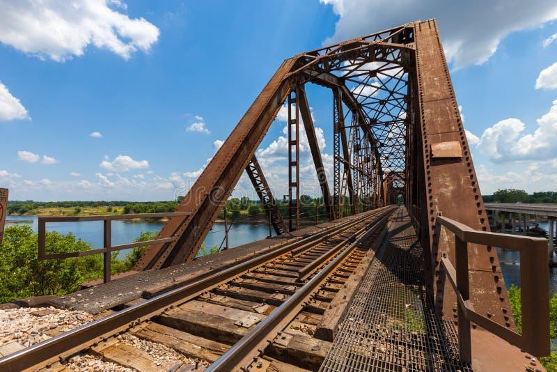 Gammal rostig bråckbandjärnvägbro över Redet River på gränsen arkivfoto