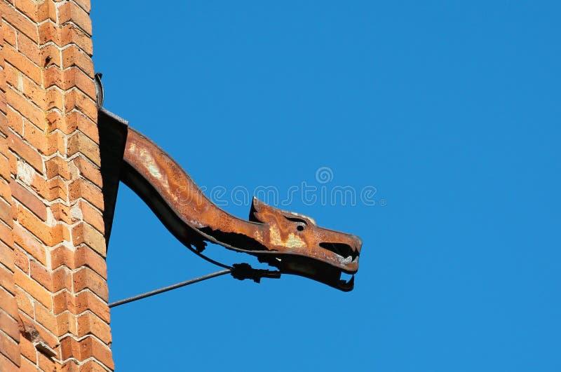Gammal rostig dekorativ avloppsränna mot bakgrund för blå himmel royaltyfri foto