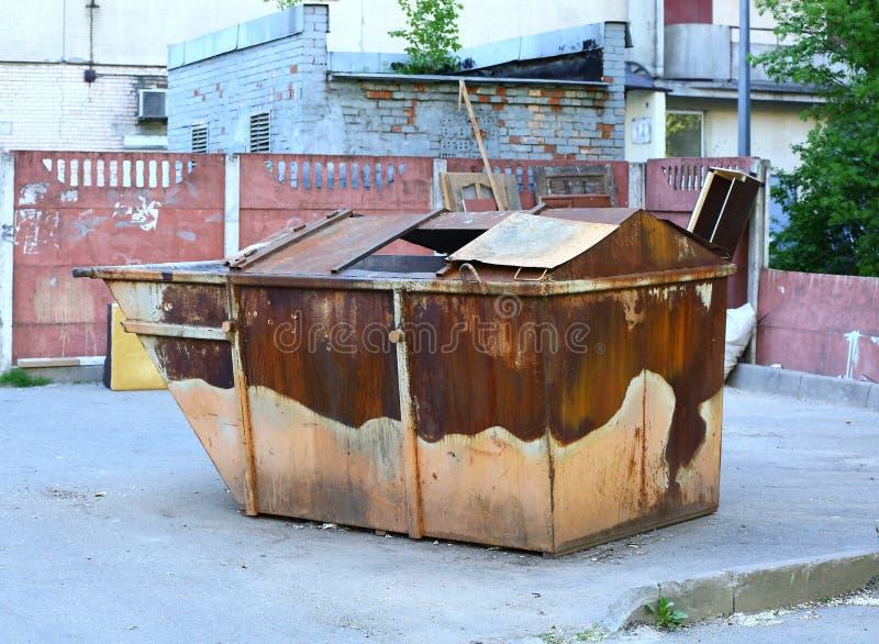Gammal rostig dumpster i gården royaltyfri foto