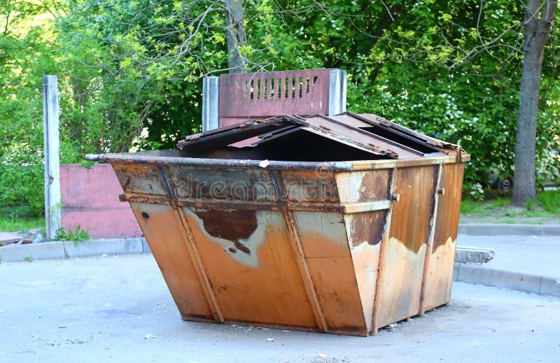 Gammal rostig dumpster i g?rden arkivfoto