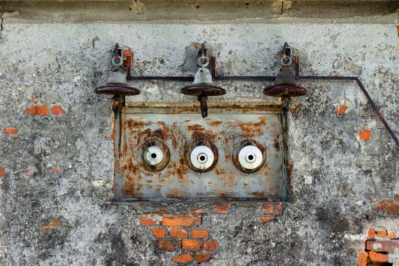 Gammal rostig elkraftlinje och säkringar på ett gammalt hus arkivbild