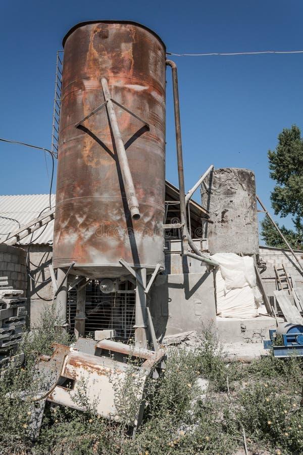 Gammal rostig industriell cementlagringsbehållare arkivbilder