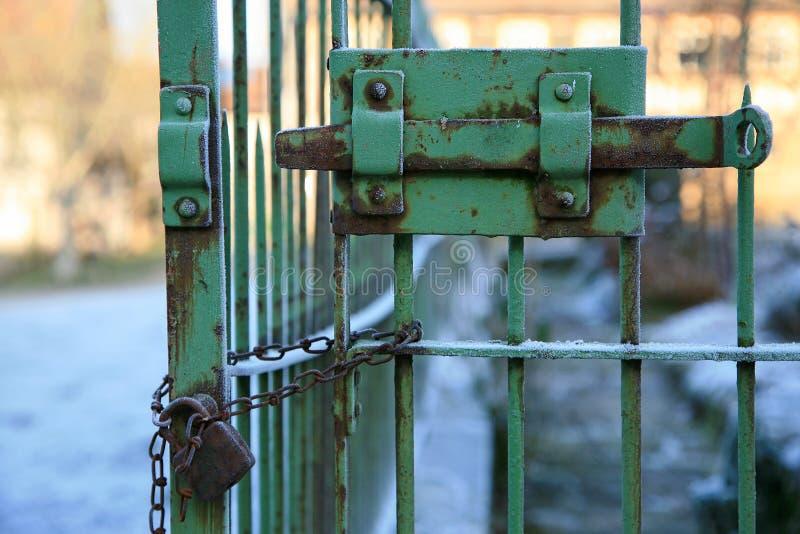 Gammal rostig järnport med att låsa stången och hänglåset med kedjan royaltyfria bilder