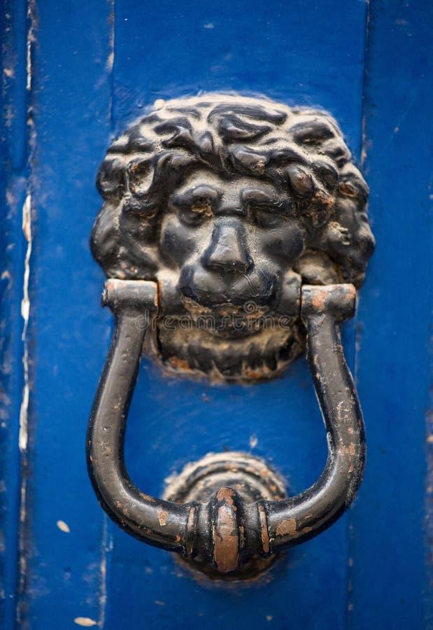 Gammal rostig knackare för dörr för järnlejonhuvud på en träazur dörr Mdina Malta arkivbild