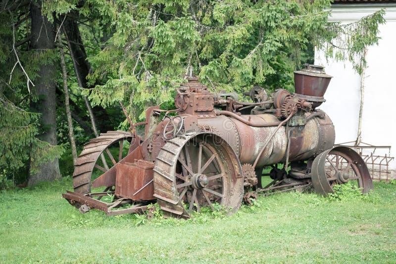 Gammal rostig lantbruktraktor arkivbild