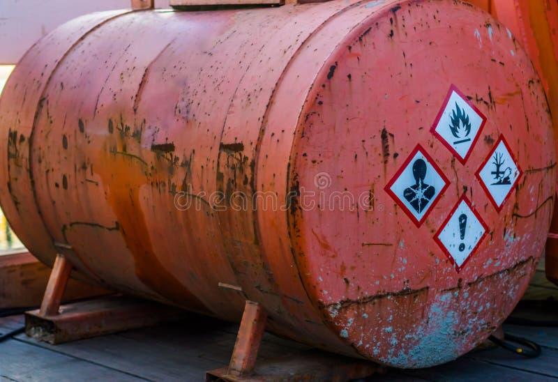 Gammal rostig silobeh?llare som inneh?ller farliga vikter, varnande etiketter p? sidan, lagring av farliga flytande royaltyfri bild
