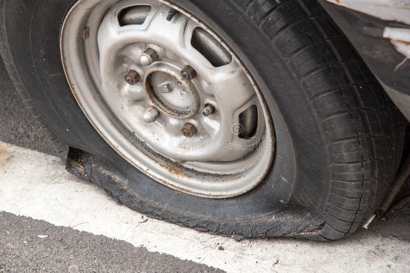 Gammal rostig skeppsbruten bil med ett punkterat gummihjul arkivbilder